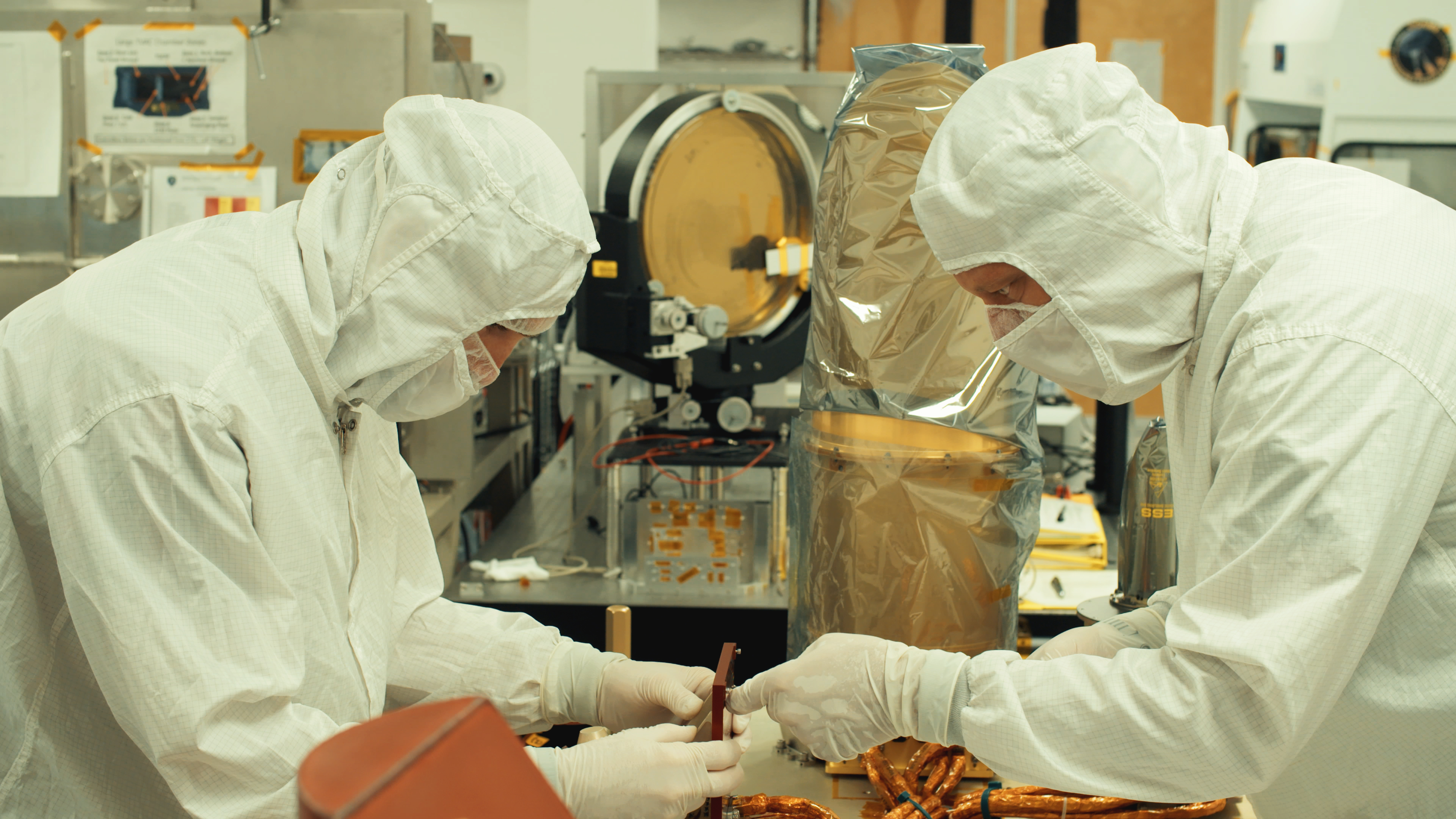 Mechanical engineer Mitch Beiser (left) and senior staff engineer William Verts prepare the OCAMS instrument for its final round of testing at UA's OSIRIS-REx facility. The camera instrument will be delivered to Lockheed Martin in Denver for installation onto NASA's OSIRIS-REx spacecraft, which is scheduled to launch into space in September 2016. Credit: University of Arizona/Symeon Platts